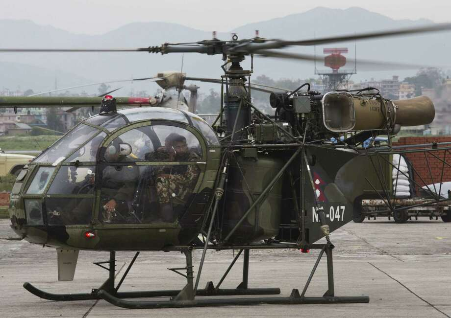 """A Nepalese army chopper, that spotted the suspected wreckage of a U.S. Marine helicopter, lands at the airport in Kathmandu, Nepal, Friday, May 15, 2015. Nepalese rescuers on Friday found three bodies near the wreckage of the chopper that was carrying six Marines and two Nepalese army soldiers. The U.S. Marines said they were sending their own rescue team to assess the wreckage and determine if it was the missing helicopter, the UH-1 """"Huey."""" Photo: (AP Photo/Bernat Armangue) / AP"""