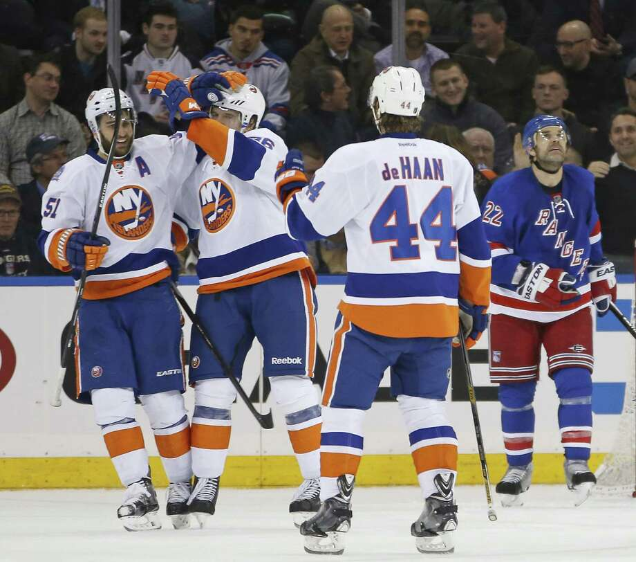 The New York Islanders' Frans Nielsen (51) celebrates with Nikolay Kulemin after scoring a goal as Rangers defenseman Dan Boyle watches a replay on a giant video screen during the Isles' 3-0 win on Tuesday night at Madison Square Garden in New York. Photo: Kathy Willens — The Associated Press  / AP
