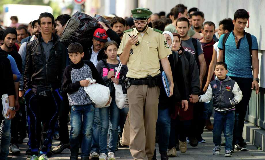 Refugees and migrants  are on their way to a asylum-seekers' accommodation  after their arrival at the main  train station in Munich, southern Germany, Saturday, Sept. 12, 2015. Photo: Sven Hoppe/dpa  Via AP  / dpa