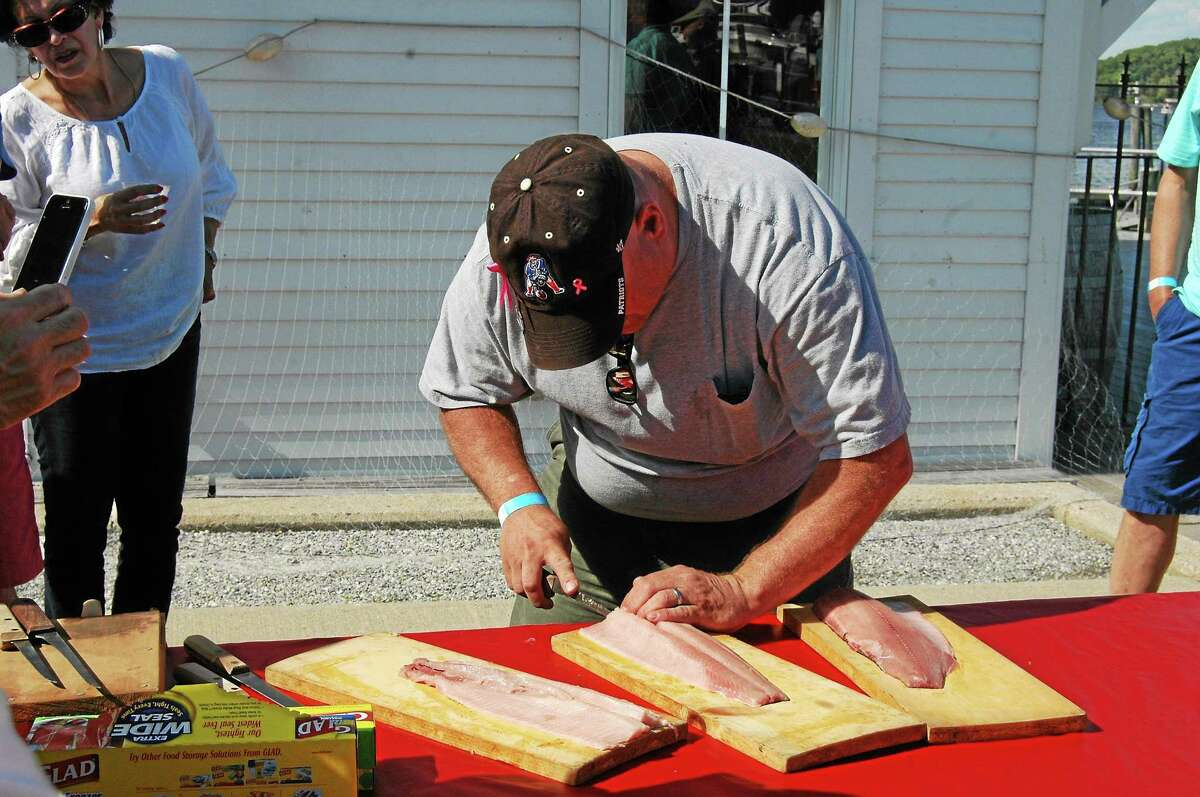 """Bill Hoffstetler demonstrates the fine art of removing bones from shad, a fish referred to by local Native Americans as the """"inside-out porcupine."""" The annual Rotary Club shad bake takes place early next month at the Connecticut River Museum in Essex"""