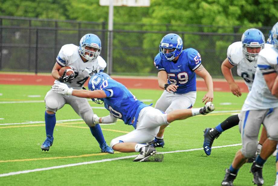 Old Saybrookís Ethan Casberg tries to elude Coginchaug defenders Carson Aitken (10) and Joe Prifitera (59) Saturday in Durham. Photo: Jimmy Zanor — Middletown Press
