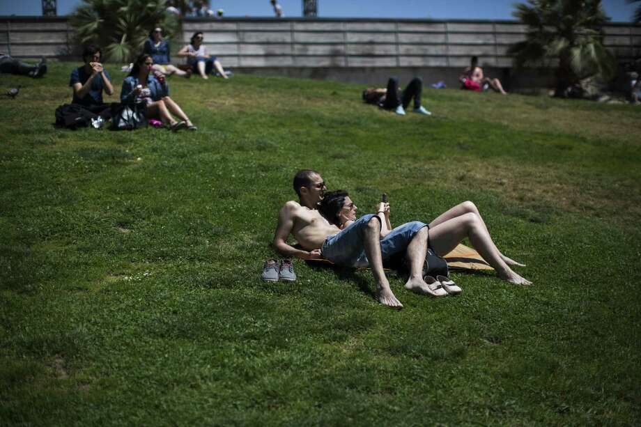 People sunbathe in a public park in Barcelona, Spain, Friday, May 15, 2015. The Iberian Peninsula has experienced record high temperatures for May as thermometers shot up to levels normally only seen in midsummer. Photo: (AP Photo/Emilio Morenatti) / AP