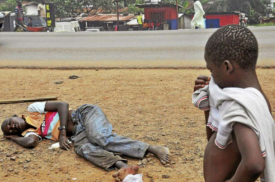 AP Photo/Abbas Dulleh A child looks at a man suspected of suffering from the Ebola virus, while holding his hand over his nose, in a main street and busy part in Monrovia, Liberia,on Sept. 12, 2014. Photo: AP / AP2014
