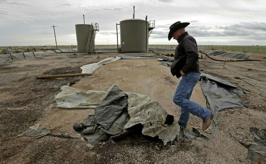 Justin Johnson looks at a torn lining at a tank and pipeline station adjacent to his ranch near Crossroads, N.M. Trucks bring oilfield wastewater to the station, where it is pumped through pipelines to a disposal well. The lining is intended to prevent wastewater from seeping into the ground in the event of a leak, but it is in poor condition. Photo: Charlie Riedel — The Associated Press  / AP