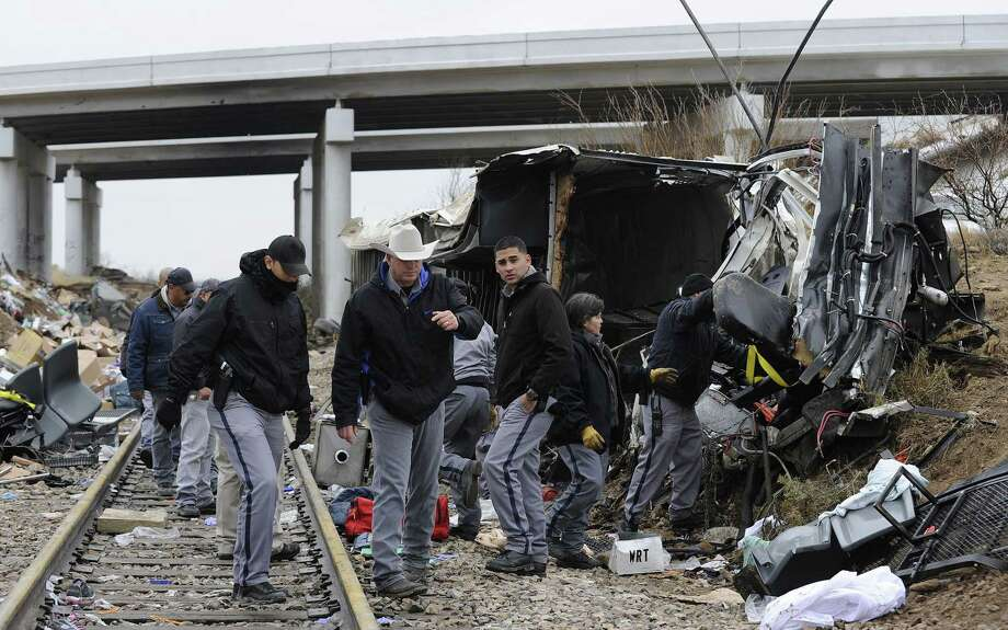 Officials investigate the scene of a prison transport bus crash, Wednesday, Jan. 14, 2015, in Penwell, Texas. Law enforcement officials said the bus carrying prisoners and corrections officers fell from an overpass in West Texas and crashed onto train tracks below, killing at least 10 people. Photo: (AP Photo/Odessa American, Mark Sterkel) / Odessa American