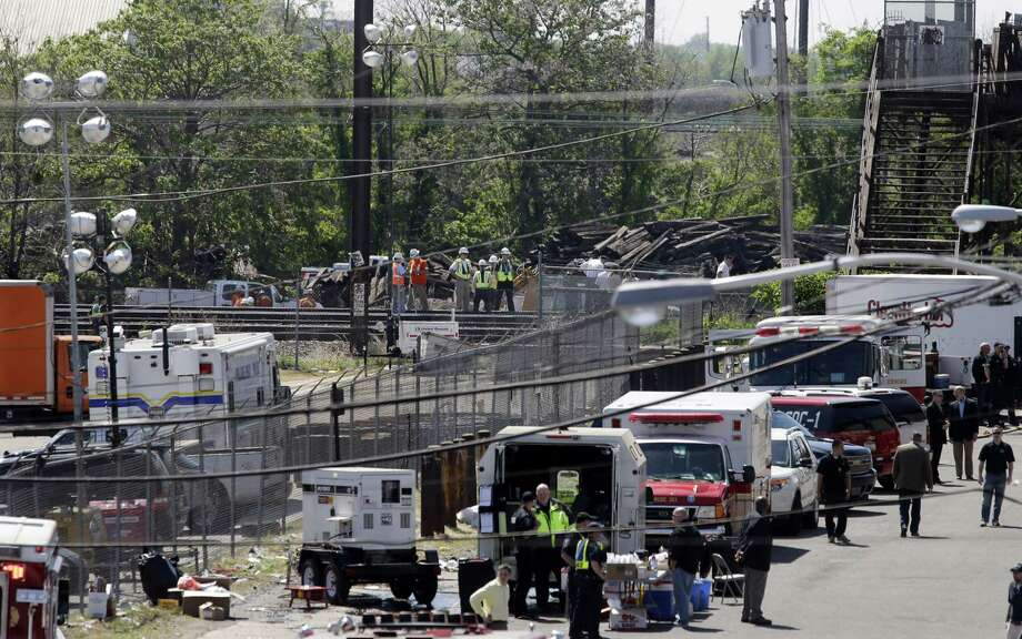 Investigators, center back, stand on the tracks near Tuesday's deadly train derailment, Thursday, May 14, 2015, in Philadelphia. An Amtrak train headed to New York City derailed and crashed in Philadelphia on Tuesday night killing at least eight people and sending more than 200 passengers and crew to area hospitals. The engineer in the deadly train derailment doesn't remember the crash, his lawyer said Thursday, complicating the investigation into why the Amtrak passenger train was going more than twice the allowed speed when it shot off a sharp curve. Photo:  (AP Photo/Mel Evans) / AP