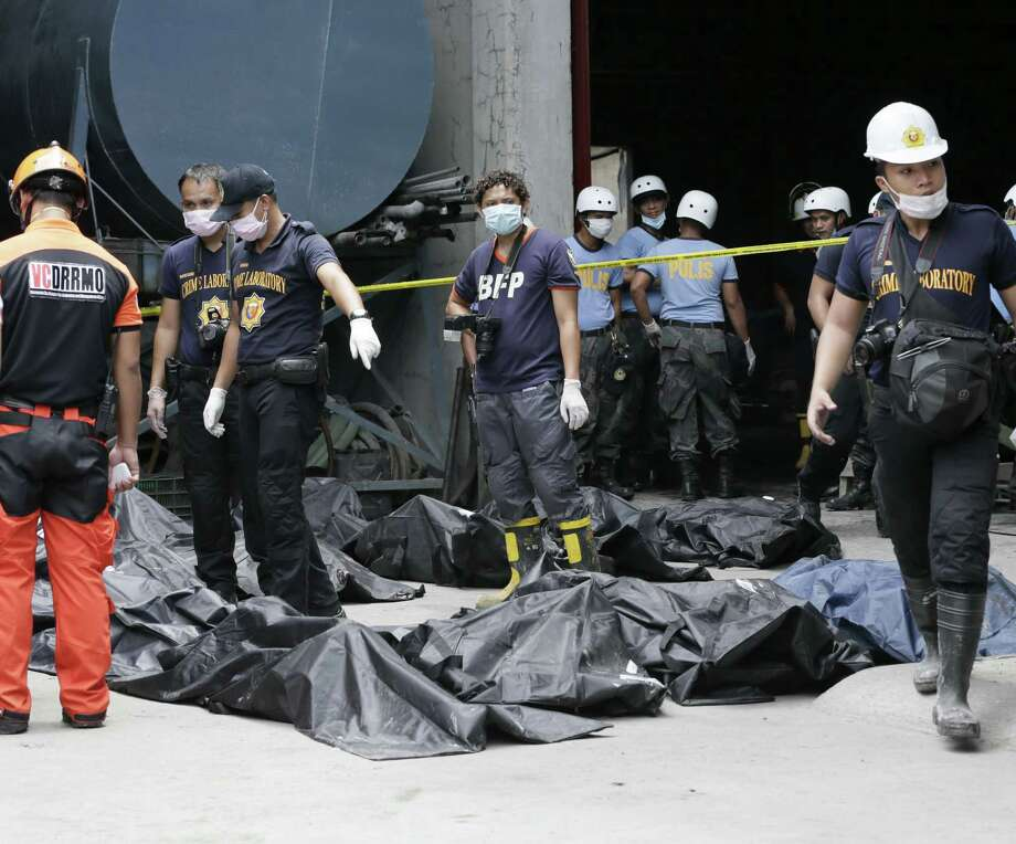 Philippine National Police stand beside the body bags of fire victims at Kentex rubber slipper factory in Valenzuela city, a northern suburb of Manila, Philippines, Thursday, May 14, 2015. On Thursday, police will open a criminal investigation into the incident that killed dozens of people, as a relative of several of the victims said the blaze had trapped workers in the building's second floor where iron grills on windows prevented their escape. Photo: (AP Photo/Bullit Marquez) / AP