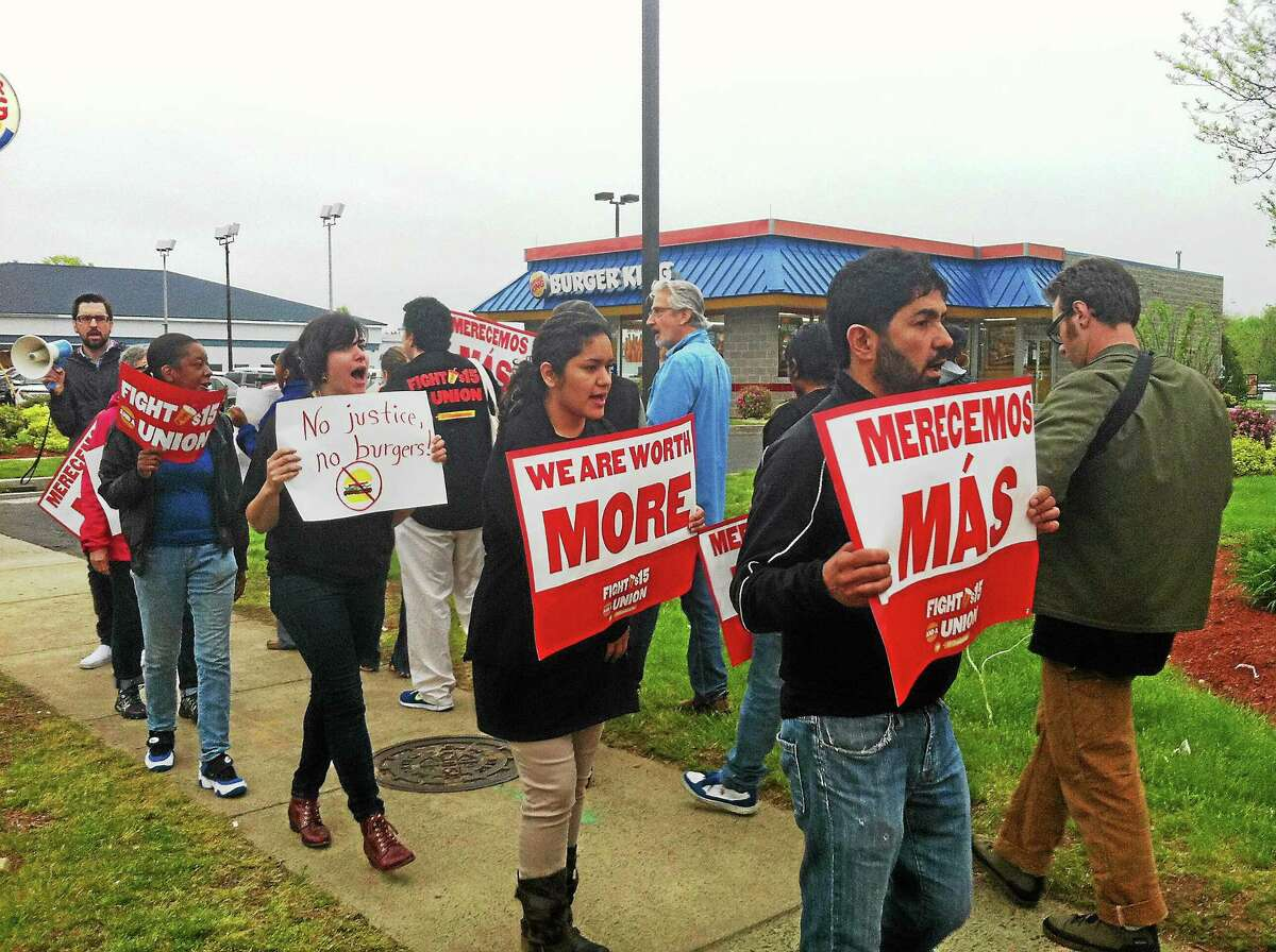 Workers, community members and advocates protest in front of the Wendy's next to a Burger King on Dixwell Avenue in Hamden on Thursday. They want fast food workers to be paid $15 per hour for their work.