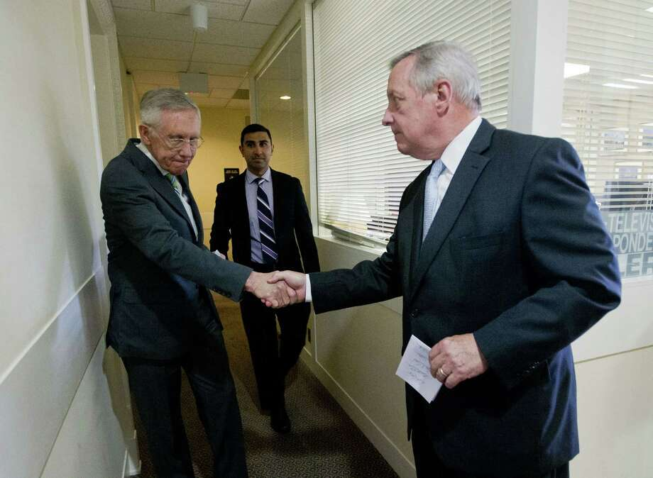 Senate Minority Leader Harry Reid of Nevada, left, shakes hands with Senate Minority Whip Richard Durbin of Illinois, right, after speaking with reporters following the Senate vote on the Iran nuclear agreement on Capitol Hill in Washington, Thursday, Sept. 10, 2015. The House is continuing to flex its muscles on the Iran nuclear deal even though the Senate has already sealed its fate in Congress.  Senate Democrats voted to uphold the hard-fought nuclear accord with Iran on Thursday, overcoming ferocious GOP opposition and delivering President Barack Obama a legacy-making victory on his top foreign policy priority. Photo: AP Photo/Pablo Martinez Monsivais  / AP