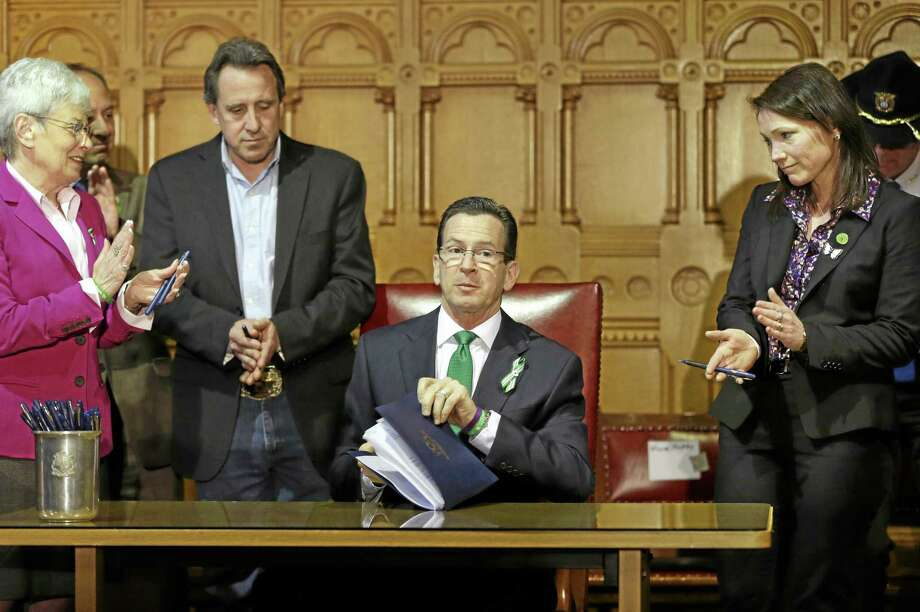 Connecticut Gov. Dannel P. Malloy, center, completes signing legislation that includes new restrictions on weapons and large capacity ammunition magazines, at the Capitol in Hartford, Conn., Thursday, April 4, 2013. Photo: Steven Senne — The Associated Press  / AP