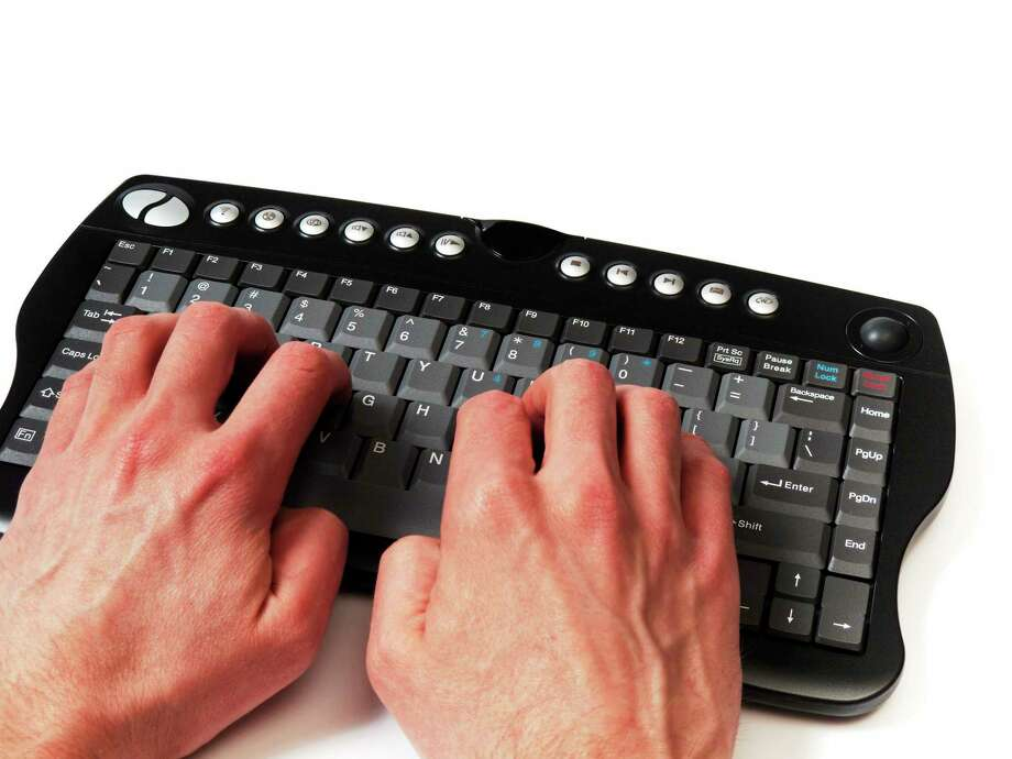 Hands in front of a compact black keyboard, on the home row, isolated on white. Photo: Journal Register Co. / iStockphoto