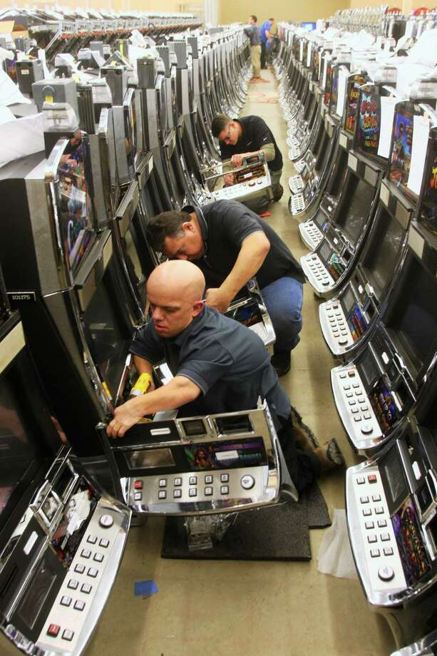JOHN HAEGER-ONEIDA DAILY DISPATCH @ONEIDAPHOTO ON TWITTER  Technicians work to ready  new, state-of-the-art cash-play slot machines, on in February 2014 in Oneida for Turning Stone Resort and Casino in New York state. Photo: Journal Register Co.