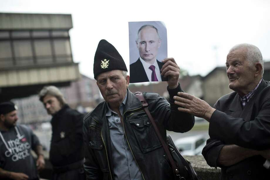 A supporter of Gen. Draza Mihajlovic, a World War II royalist guerrilla commander, holds a photo of Vladimir Putin, the Russian president, as he stands in front of the Higher Court in Belgrade, Serbia, Thursday, May 14, 2015. A Belgrade court on Thursday quashed the treason conviction of Mihailovic for his collaboration with Nazis during World War II, politically rehabilitating the controversial Serbian guerrilla commander almost 70 years after he was sentenced and shot to death by communists. Photo: (AP Photo/Marko Drobnjakovic) / AP