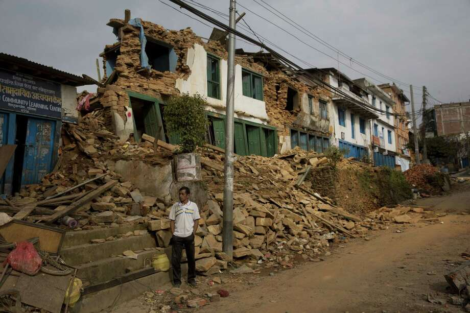 A man inspects an area that was severely affected in the May 12 earthquake stands tilted in Chautara, Nepal, Wednesday, May 13, 2015. Thousands of fear-stricken people spent the night outdoors after a new earthquake killed dozens of people and spread more misery in Nepal, which is still reeling from a devastating quake that killed thousands nearly three weeks ago. Photo: (AP Photo/Bernat Amangue) / AP