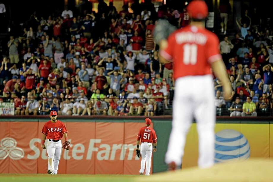 Rangers starting pitcher Yu Darvish watches from the mound as Rougned Odor, left rear, and right fielder Alex Rios, right rear, walk back to their positions after a ball fell between them allowing Boston Red Sox DH David Ortiz to reach first in the seventh inning of a baseball game on Friday in Arlington, Texas. Photo: Tony Gutierrez — The Associated Press  / AP