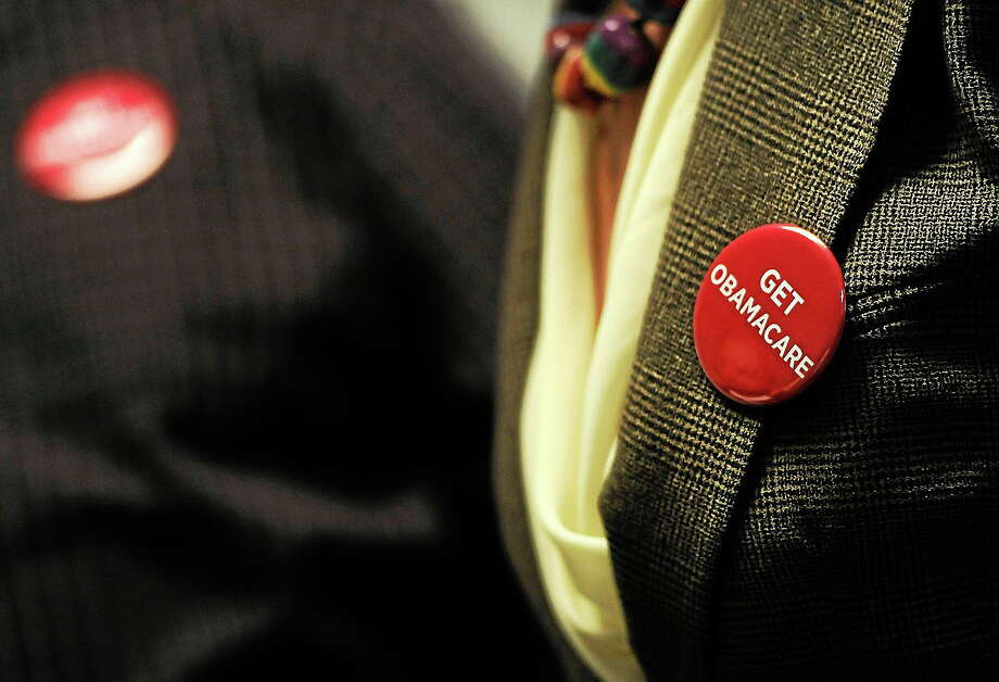 """Associates at Community Health Center wear buttons reading """"Get Obamacare"""" during a session to enroll people in the nationís new health insurance system at the Community Health Center, Tuesday, Oct. 1, 2013, in New Britain, Conn. Photo: AP Photo/Jessica Hill  / FR125654 AP"""