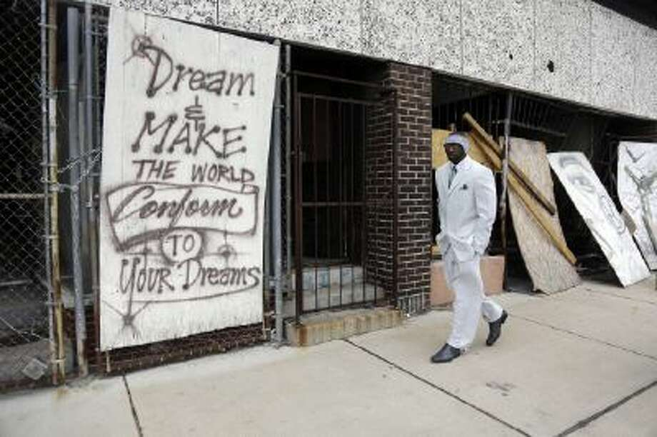 Melvin White, founder of the Beloved Streets of America project, walks past a boarded up building during a tour of Dr. Martin Luther King Jr. Drive in St. Louis.