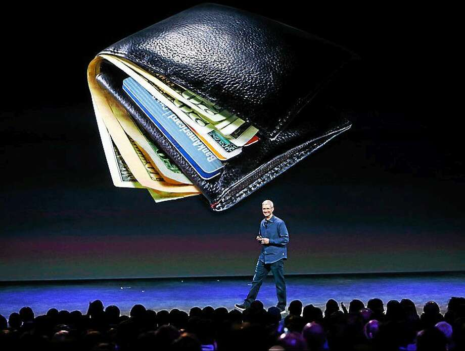 Apple CEO Tim Cook, standing in front of an image of bulging wallet, begins to describe a new way to pay, while introducing the iPhone 6 and the Apple Watch at the Flint Center in Cupertino, Calif., on Sept. 9, 2014. Photo: Karl Mondon/Bay Area News Group  / """"