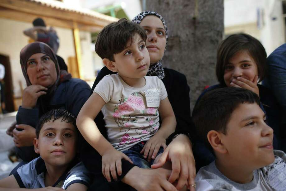 Syrians sit on a sidewalk in Izmir, Turkey, Thursday, Sept. 10, 2015. While migrants for years have taken death-defying trips across the Mediterranean to reach the relative peace and comfort of the European Union, the flow has hit record proportions this year _ notably with an influx of Syrians, Afghans and Eritreans fleeing trouble back home. Photo: AP Photo/Emrah Gurel   / AP