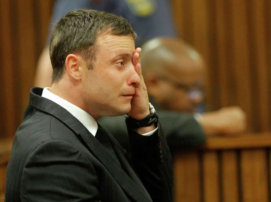 Oscar Pistorius cries in the dock in Pretoria, South Africa, Thursday, Sept. 11, 2014 as Judge Thokozile Masipa reads notes as she delivers her verdict in Pistorius' murder trial. The verdict is expected to take hours and possibly two days to present. She will decide with the help of two legal assessors if Pistorius is guilty of the murder of his girlfriend Reeva Steenkamp. (AP Photo/Kim Ludbrook, Pool) Photo: AP / POOL EPA