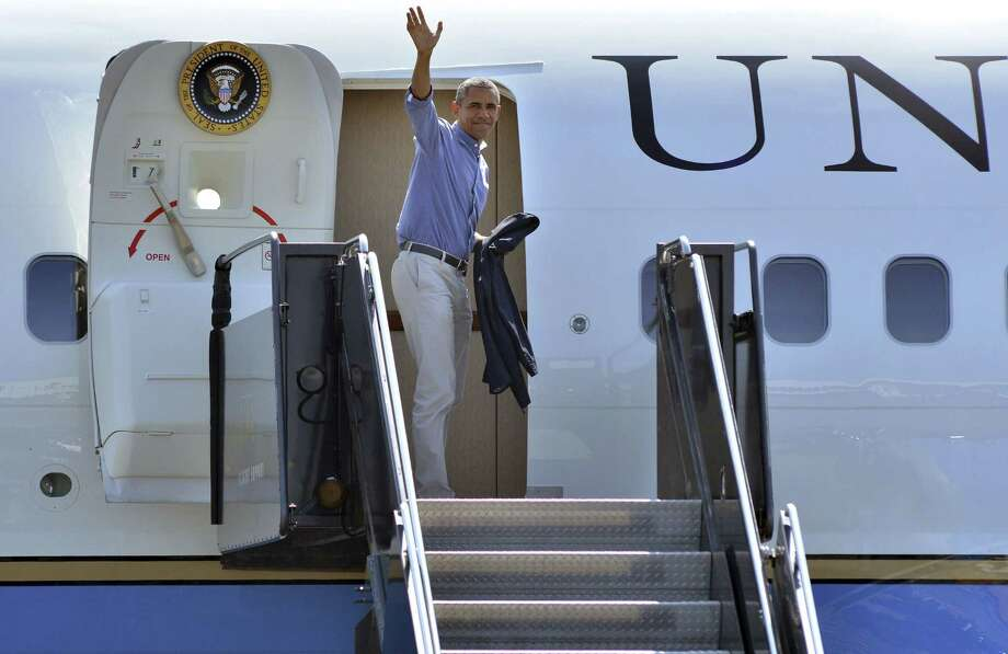 President Barack Obama waves before boarding Air Force One to depart from Logan Airport in Boston on Labor Day, Monday, Sept. 7, 2015. Obama has said he would like the U.S. to accept 10,000 Syrian refugees this coming budget year. Photo: AP Photo/Josh Reynolds   / FR25426 AP