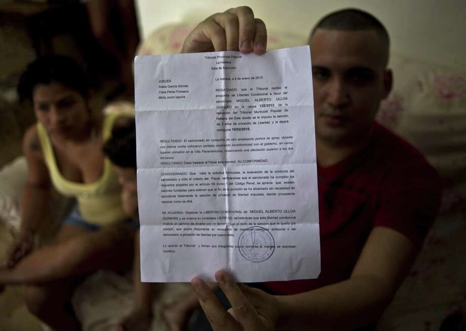 Dissident Miguel Alberto Ulloa, 25, poses for a photo in his home, holding his release document, a day after his release, in Havana, Cuba on Jan. 9, 2015. Photo: AP Photo/Ramon Espinosa  / AP