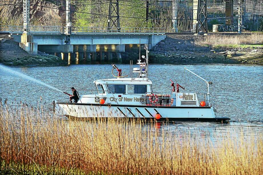 Marine 1 is used at the scene of a brush fire along the banks of the West River Thursday. Photo: Catherine Avalone — New Haven Register  / New Haven RegisterThe Middletown Press