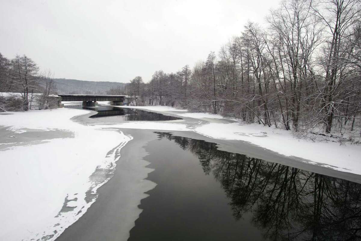 The Huron River in Ann Arbor, Mich., is covered in snow and begins to freeze over, Monday,
