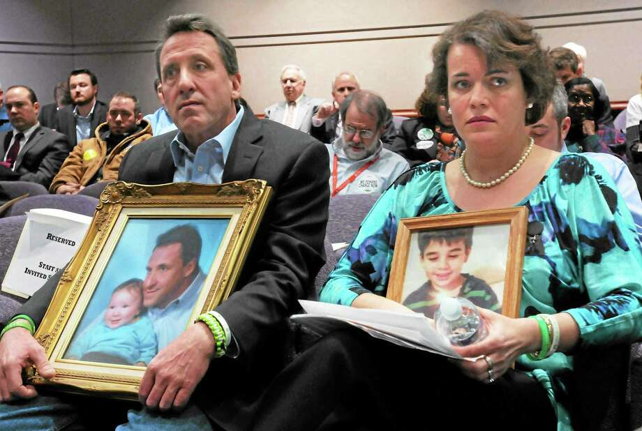 Neil Heslin, left, father of Jesse Lewis, and Veronique Pozner, mother of Noah Pozner, listen to gun manufacturers testify Jan. 27, 2013 at the Legislative Office Building in Hartford during the legislature's Gun Violence Prevention Task Force hearing. Photo: File Photo — New Haven Register