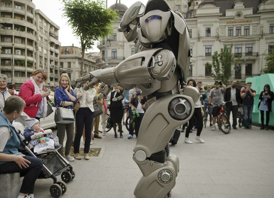 A child looks up at Titan the Robot in Bucharest, Romania on May 11, 2015. Photo: AP Photo/Vadim Ghirda  / AP
