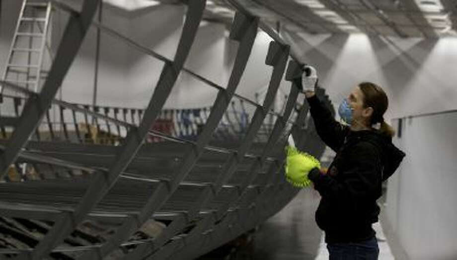 A conservator helps with the final assembly of the Viking ship known as Roskilde 6, of which about 20 percent of the timber remains and which is dated to around 1025 AD, at the British Museum in London, Friday, Jan. 17, 2014.