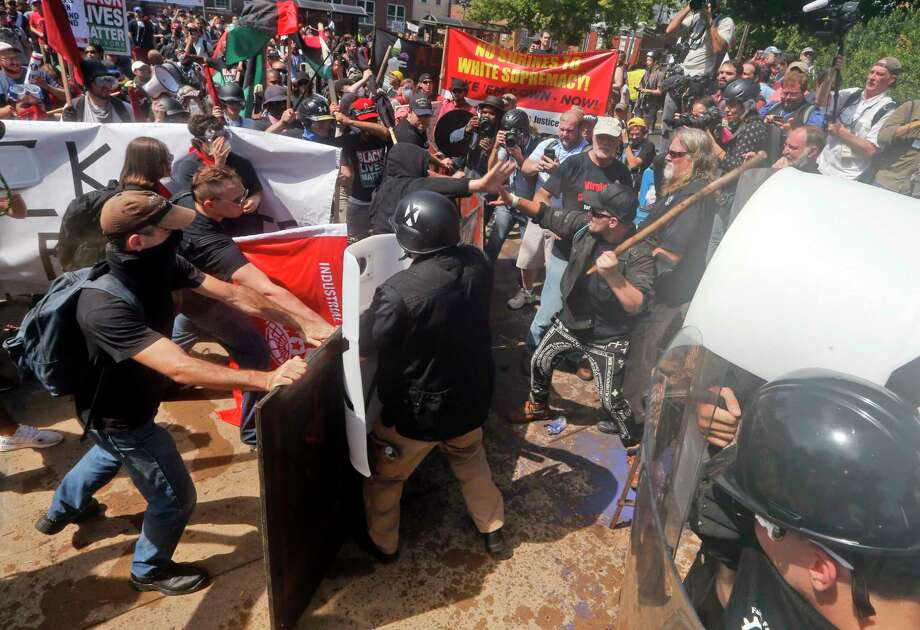 White nationalist demonstrators clash with counter demonstrators at the entrance to Lee Park in Charlottesville, Va., Saturday, Aug. 12, 2017. Gov. Terry McAuliffe declared a state of emergency and police dressed in riot gear ordered people to disperse after chaotic violent clashes between white nationalists and counter protestors. Photo: Steve Helber, AP / Copyright 2017 The Associated Press. All rights reserved.