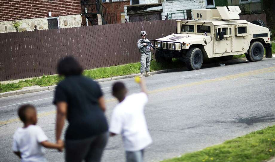 A member of the National Guard stands watch outside a neighborhood next to the Mondawmin Mall following Freddie Gray's funeral, as a mother passes with her children. Photo: AP Photo  / AP