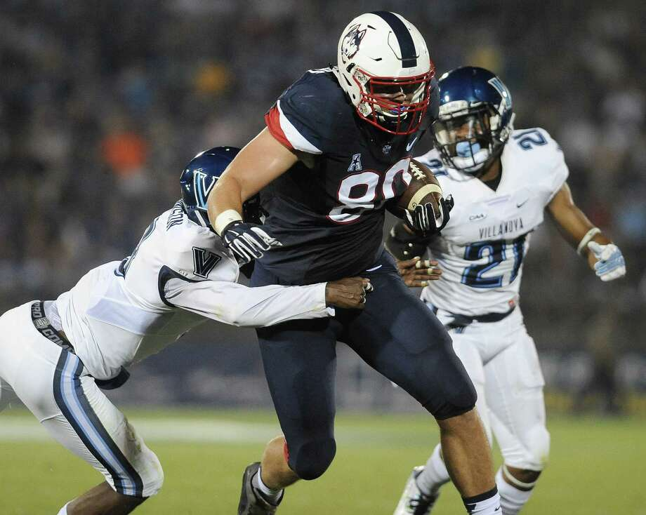 Connecticut tight end Tommy Myers (80) pulls away from Villanova defensive back Trey Johnson (8), left, for a touchdown, as Wesley Smith, right, pursues during the first half of an NCAA college football game at Rentschler Field, Thursday, Sept. 3, 2015, in East Hartford, Conn. (AP Photo/Jessica Hill) Photo: AP / FR125654 AP