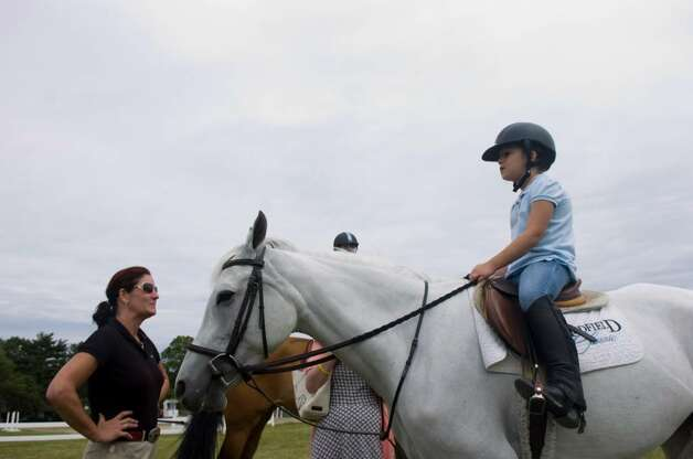 Theresa Bowling and her daughter Avery, 7, take Bella out for a spin during the 80th Ox Ridge June Show June 16, 2010. The show runs through Sunday. Photo: Keelin Daly / Stamford Advocate