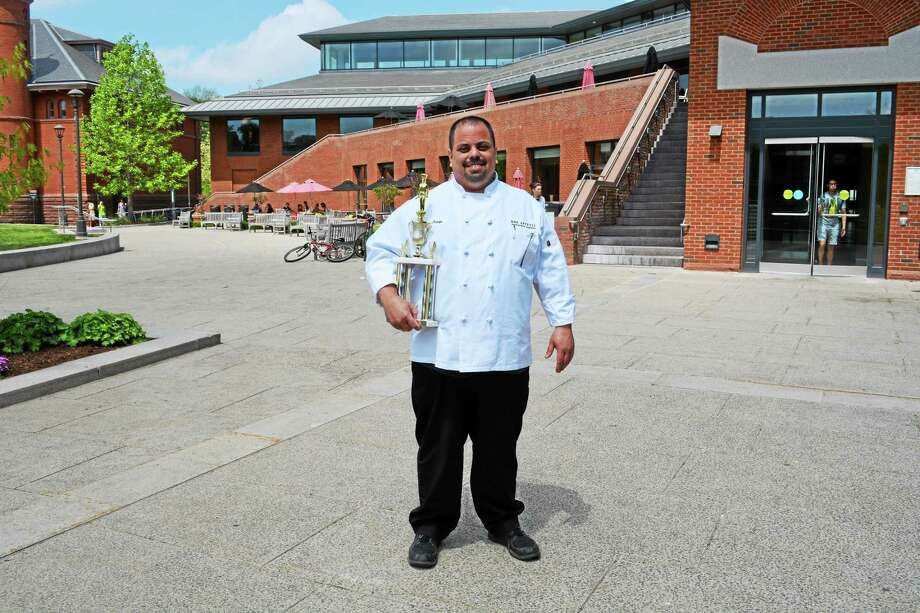 Chef Ernie Arroyo stands outside the Wesleyan Dining Hall with his trophy for 2014 Chef of the Year. Photo: Brian Zahn — The Middletown Press