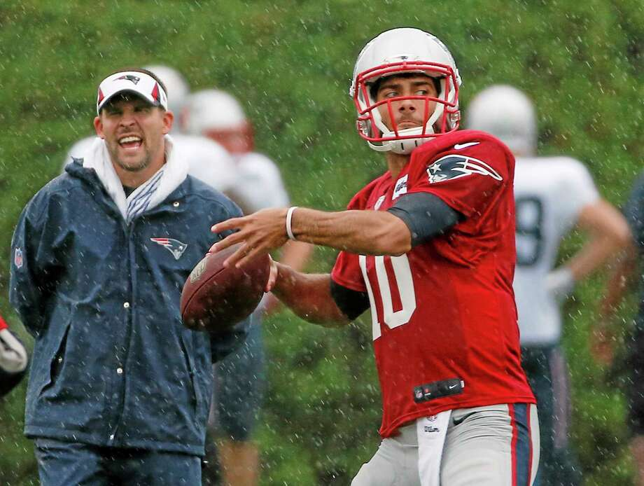 New England Patriots quarterback Jimmy Garoppolo passes while offensive coordinator Josh McDaniels watches during an August practice. Photo: Elise Amendola — The Associated Press  / AP