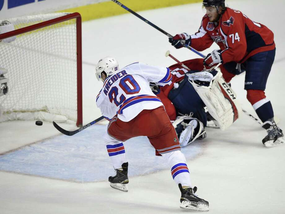 Rangers left wing Chris Kreider scores his second goal of the first period past Washington Capitals goalie Braden Holtby on Sunday. Photo: Nick Wass — The Associated Press  / FR67404 AP
