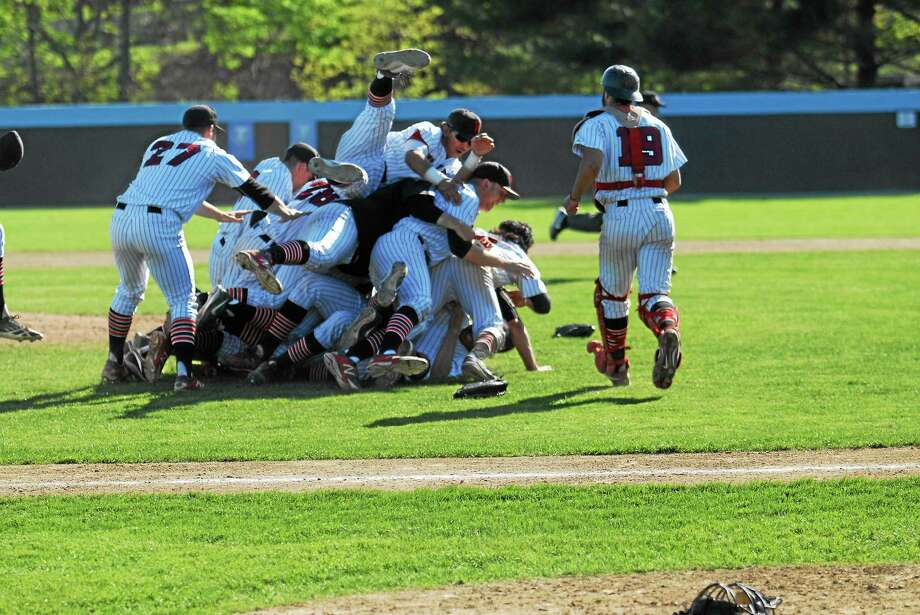 Wesleyan players celebrate after capturing their first ever NESCAC tournament championship with a 6-4 win over Tufts Sunday in Medford (Mass.). Photo: Jimmy Zanor — Middletown Press
