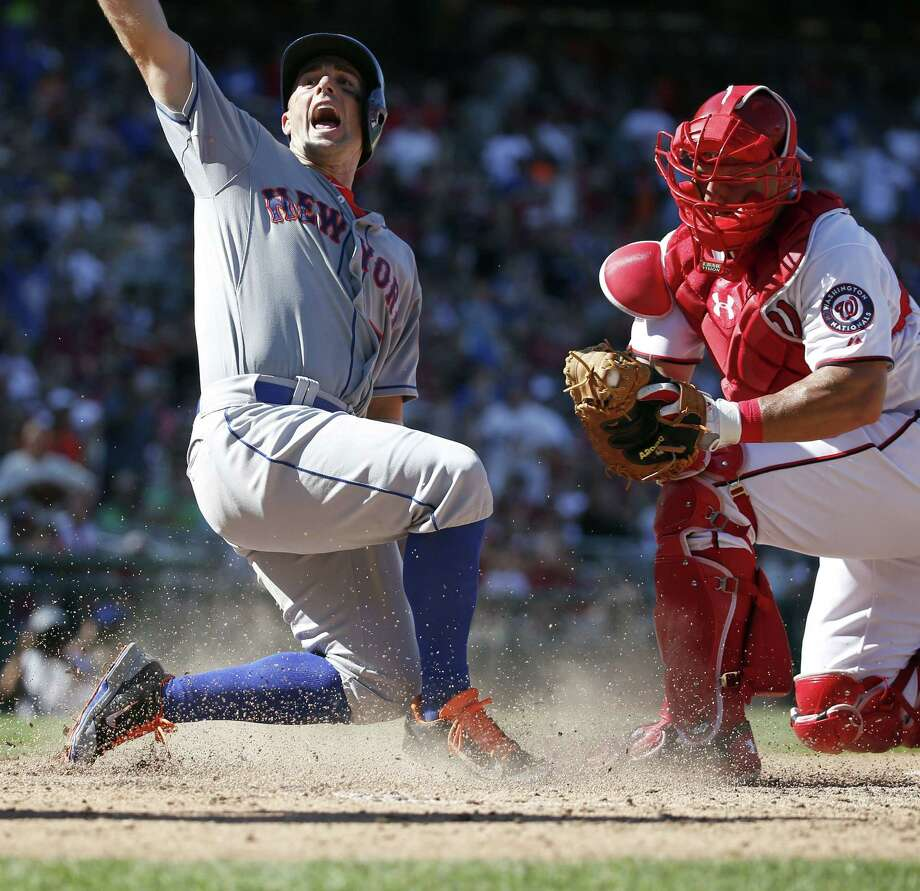 The New York Mets' David Wright, left, reacts as he scores after Nationals catcher Wilson Ramos was late with the tag during the seventh inning of Monday's game at Nationals Park in Washington. Photo: Alex Brandon — The Associated Press  / AP