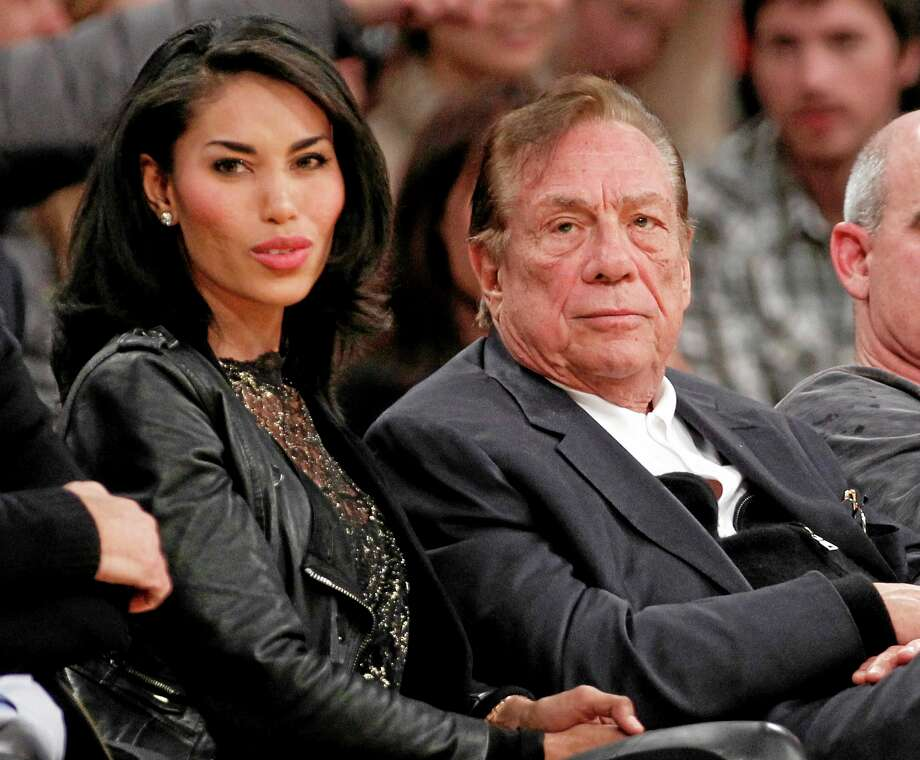 FILE - In this Dec. 19, 2010, file photo, Los Angeles Clippers owner Donald Sterling, third right, sits with V. Stiviano, left, as  they watch the Clippers play the Los Angeles Lakers during an NBA preseason basketball game in Los Angeles. NBA commissioner Adam Silver announced Tuesday, April 29, 2014, that he is banning the owner for life from the Clippers organization over racist comments in recording. (AP Photo/Danny Moloshok, File) Photo: AP / FR161655 AP