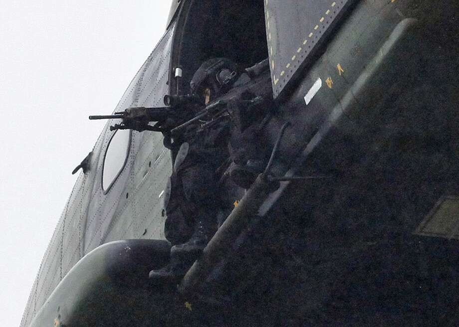 Armed security forces fly overhead in a military helicopter  in Dammartin-en-Goele, northeast of Paris, Friday Jan. 9, 2015.   French security forces swarmed this small industrial town northeast of Paris Friday in an operation to capture a pair of heavily armed suspects in the deadly storming of a satirical newspaper. (AP Photo/Thibault Camus) Photo: AP / AP