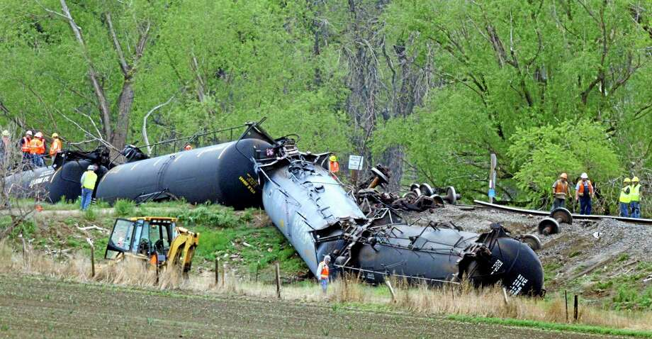 Crews work to clean up several train cars that were derailed and flipped along the track southwest of LaSalle, Colo. on Friday, May 9, 2014. The train, loaded in Windsor with Niobrara crude bound for New York, derailed around 8 a.m. according to Union Pacific Spokesman Mark Davis. Officials found one car of the 100-car train was leaking. (AP Photo/The Greeley Tribune, Joshua Polson) Photo: AP / The Greeley Tribune