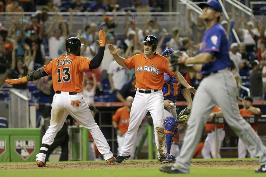The Marlins' J.T. Realmuto, center, is congratulated by teammate Marcell Ozuna (13) after scoring the winning run against the Mets on Sunday. Photo: Alan Diaz — The Associated Press  / AP