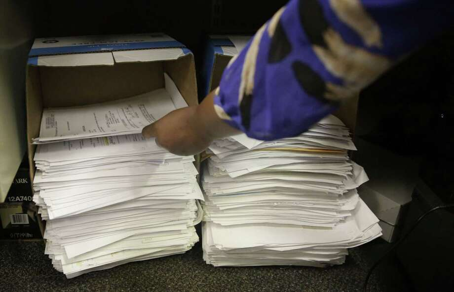 Stacks of documents gather under court specialist Trameka Daniels' desk daily at the Alabama Circuit Court Clerk Criminal office on May 7, 2015 in Montgomery, Ala. A trend is emerging among states like Alabama showing large budget gaps. Photo: AP Photo/Brynn Anderson  / AP