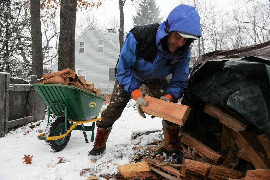 Dan Pine of New Paltz, New York, stacks wood in a wheelbarrel to load into his furnace in this file photo. Photo: File Photo