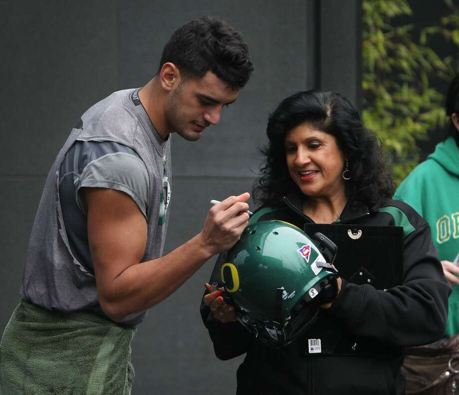 Oregon quarterback Marcus Mariota, left, signs an autograph for a fan after Wednesday's practice in Eugene, Ore. Photo: Chris Pietsch — The Register-Guard  / The Register-Guard
