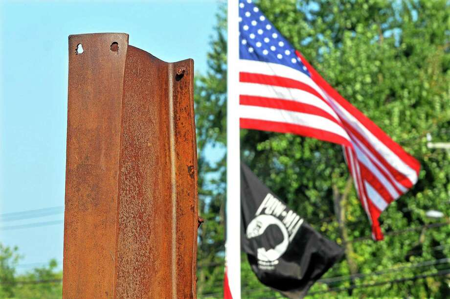 The American flag waves behind the 8-foot beam, the centerpiece of the Memorial Garden from the North Tower South District Fire Department 9/11 Remembrance and Memorial Garden dedication in this file photo. Photo: Catherine Avalone - The Middletown Press File Photo  / TheMiddletownPress