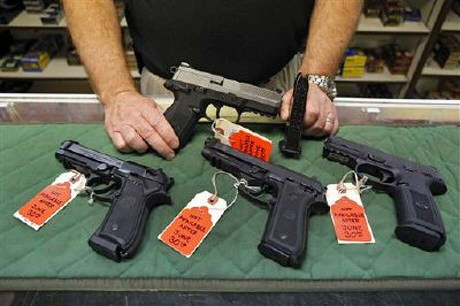 A store manager in Aurora, Colo., shows some of the pistols that he won't be able to sell under new gun laws in Colorado because their magazines hold more than 15 rounds. Photo: AP / AP