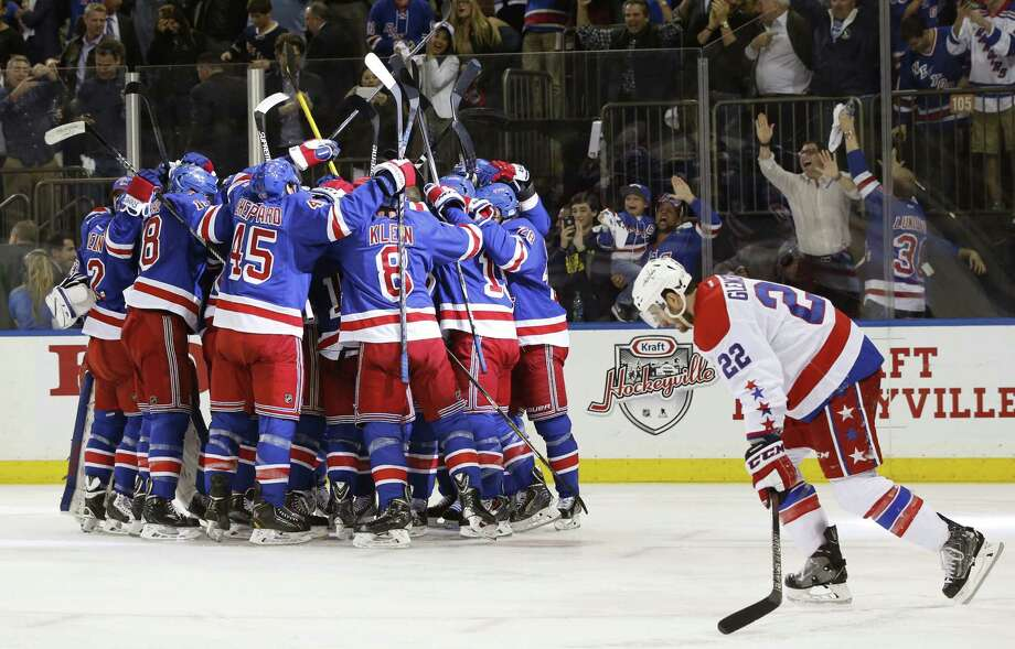 Capitals left wing Curtis Glencross (22) skates past the New York Rangers as they celebrate their 2-1 overtime victory over the Capitals in Game 5 on Friday night. Photo: Kathy Willens — The Associated Press  / AP